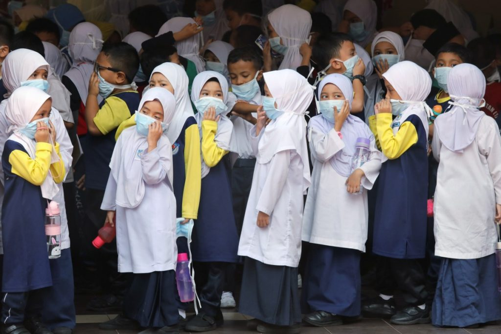 Students cover their faces with masks at a school as haze shrouds Kuala Lumpur, Malaysia. Photo: Reuters